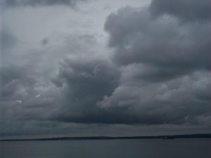 A photo of dramatic grey clouds above the sea, with a long and thin island on the horizon.